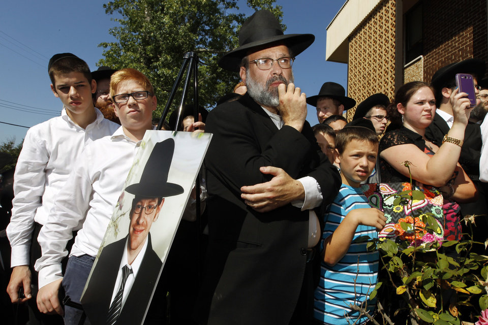 Photo - A photograph of Aaron Sofer, 23, is nearby as people listen during a news conference Tuesday, Aug. 26, 2014, in Lakewood, N.J. Israeli police said Tuesday they are searching for the young New Jersey religious student who went missing during a hike in a forest outside Jerusalem last week. Sofer of Lakewood, New Jersey, has been missing since Friday when he went on a hike with a friend in the Jerusalem Forest, said police spokesman Micky Rosenfeld. Rosenfeld said that police have launched an extensive search for Sofer, who is an ultra-Orthodox student at a yeshiva — a Jewish religious school. Sofer's parents have flown to Israel. (AP Photo/Mel Evans)