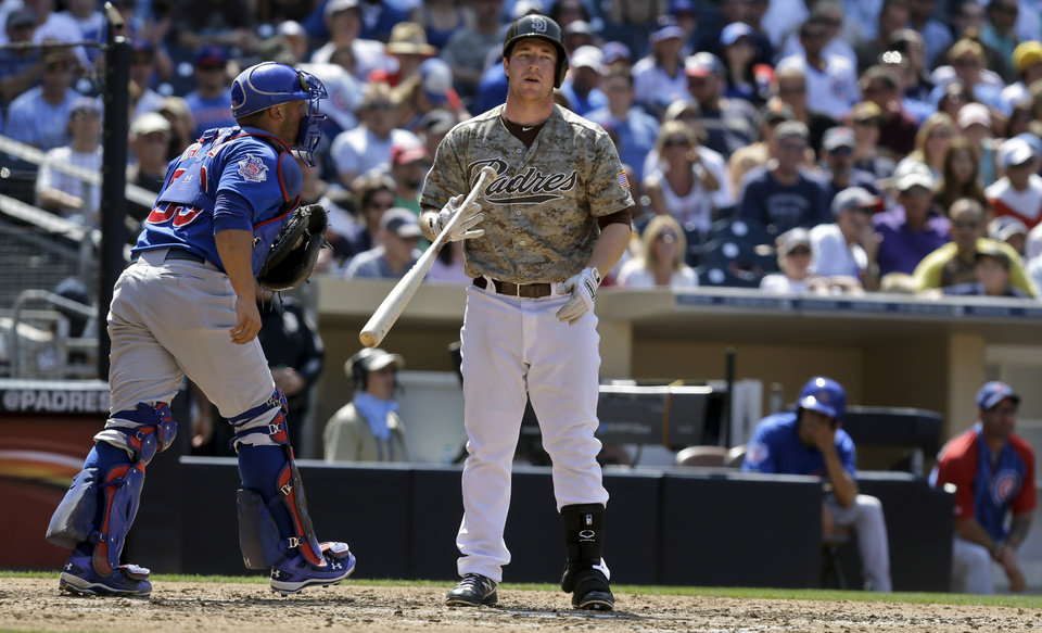 Photo - San Diego Padres' Jedd Gyorko, right, drops his bat as Chicago Cubs catcher Welington Castillo heads for the dugout after Gyorko was called out on strikes with a runner on base to end the sixth inning of a scoreless baseball game, Sunday, Aug. 25, 2013, in San Diego. (AP Photo/Lenny Ignelzi)