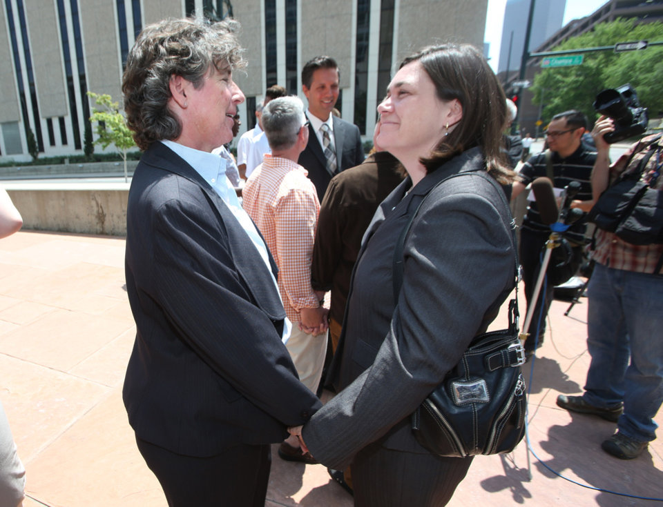 Photo - Two plaintiffs in a lawsuit to overturn Colordo's gay marriage ban, Cassie Rubald, left, and her partner, Rachel Catt, hold hands during a news conference outside the federal courthouse in downtown Denver on Tuesday, July 1, 2014. Six gay couples filed the lawsuit to ask for an injunction to stop all officials from enforcing the ban on gay marriage in Colorado. (AP Photo/David Zalubowski)