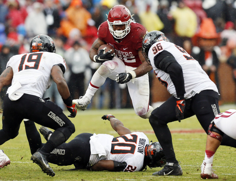 Photo - Oklahoma's Samaje Perine (32) leaps over Oklahoma State's Jordan Burton (20) near Justin Phillips (19) and Vincent Taylor (96) during the Bedlam college football game between the Oklahoma Sooners (OU) and the Oklahoma State Cowboys (OSU) at Gaylord Family - Oklahoma Memorial Stadium in Norman, Okla., Saturday, Dec. 3, 2016. OU won 38-20. Photo by Nate Billings, The Oklahoman