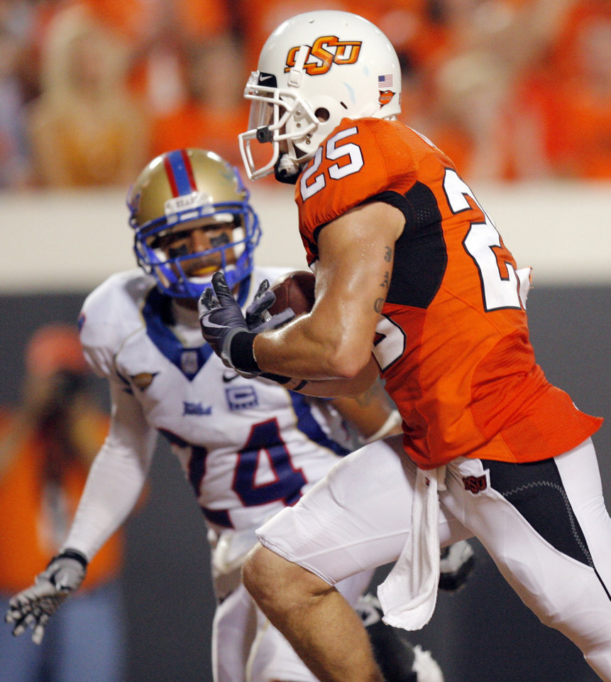 Photo - OSU's Josh Cooper (25) makes a touchdown catch in front of TU's Charles Davis (24) in the second quarter during the college football game between the University of Tulsa (TU) and Oklahoma State University (OSU) at Boone Pickens Stadium in Stillwater, Oklahoma, Saturday, September 18, 2010. Photo by Nate Billings, The Oklahoman
