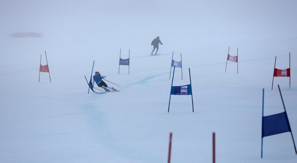 Photo - A skier skis down the fog shrouded alpine skiing training slopes at the Sochi 2014 Winter Olympics, Monday, Feb. 17, 2014, in Krasnaya Polyana, Russia. (AP Photo/Alessandro Trovati)