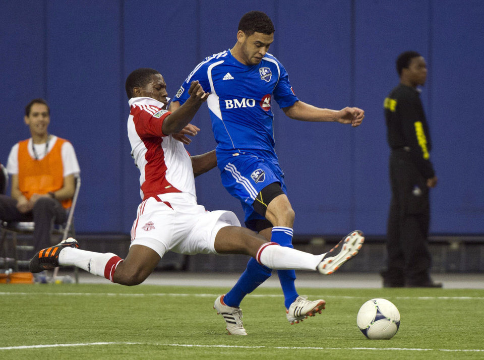 Toronto FC\'s Joao Plata stretches to knock the ball away from Montreal Impact\'s Lamar Neagle during the first half of an Amway Canadian Championship soccer match, Wednesday, May 2, 2012, in Montreal. (AP Photo/The Canadian Press, Paul Chiasson)