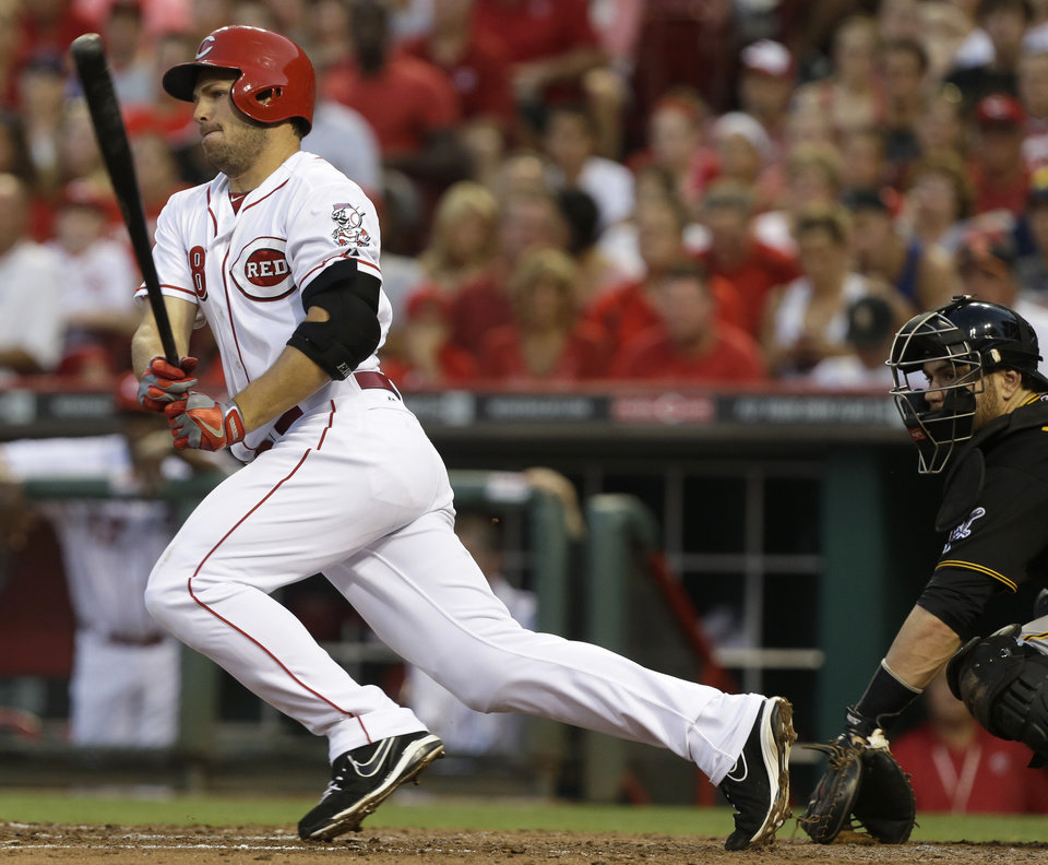 Photo - Cincinnati Reds' Chris Heisey gets a hit off Pittsburgh Pirates starting pitcher Francisco Liriano to drive in a run in the fifth inning of a baseball game, Friday, July 19, 2013, in Cincinnati. Russell Martin catches at right. (AP Photo/Al Behrman)