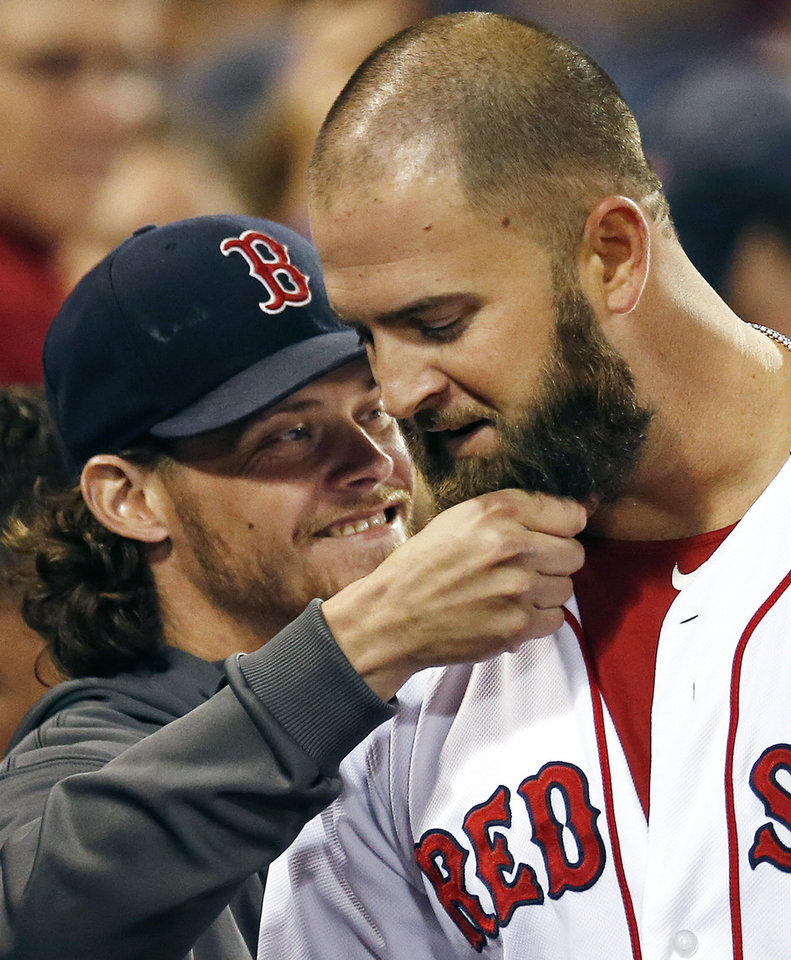 Boston Red Sox's Clay Buchholz, left, tugs on Mike Napoli's beard in the dugout after Napoli's solo home run in the sixth inning of a baseball game against the Baltimore Orioles at Fenway Park in Boston, Wednesday, Sept. 18, 2013. (AP Photo/Elise Amendola)