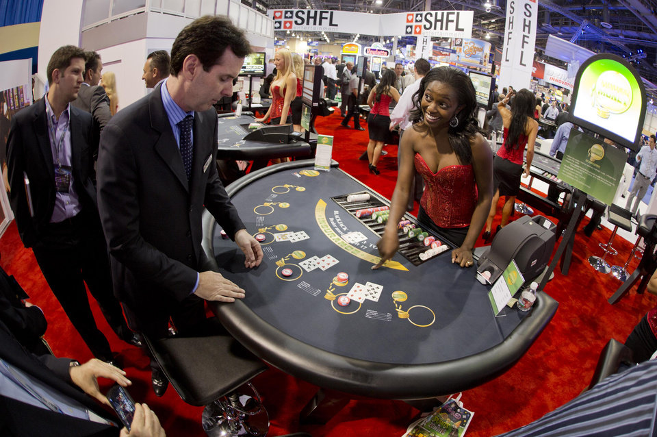 Casino industry professionals demonstrate a version of Blackjack during the Global Gaming Expo, Tuesday, Oct. 2, 2012, in Las Vegas. Casino revenues have increased this year in 18 of the 21 states that allow commercial gambling and, new casinos are opening in several jurisdictions. (AP Photo/Julie Jacobson)