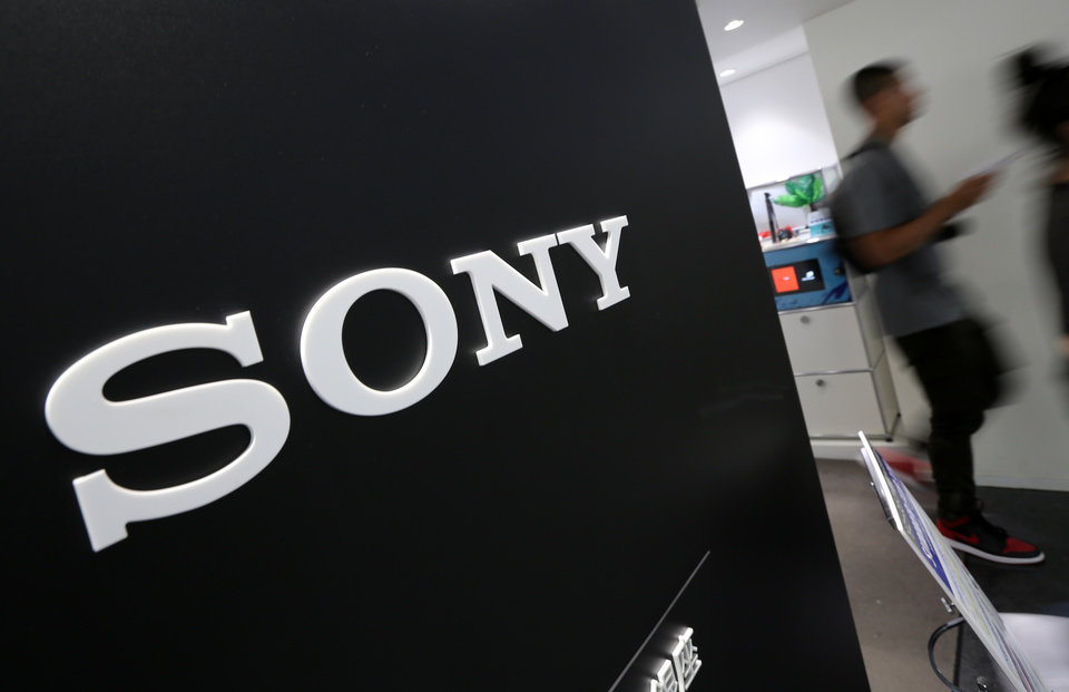 Photo - Visitors walk past a logo of Sony at Sony Building in Tokyo Thursday, July 31, 2014. Sony reported a surprise eightfold jump in quarterly profit as sales got a perk from a cheap yen and its bottom line was helped by gains from buildings and its stake in a video-game maker. (AP Photo/Eugene Hoshiko)