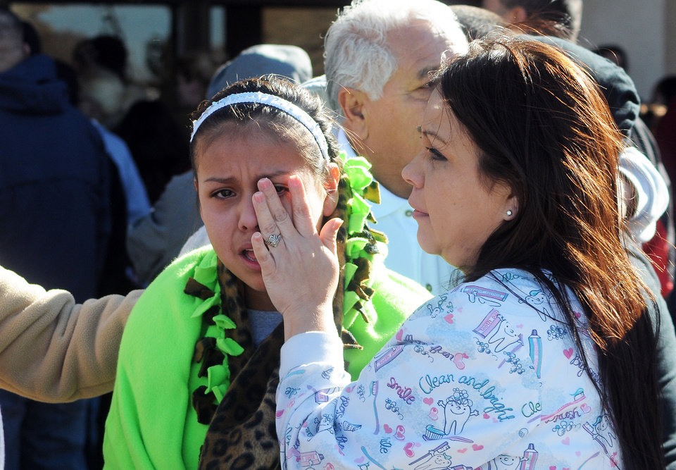 Photo - A woman wipes a girl's eyes at a staging ground area set up at the Roswell Mall, where families were united after a shooting at Berrendo Middle School, Tuesday, Jan. 14, 2014, in Roswell, N.M. A shooter opened fire at the middle school, injuring at least two students before being taken into custody. (AP Photo/Roswell Daily Record, Mark Wilson)
