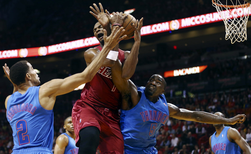 Photo - Oklahoma City Thunder'S Thabo Sefolosha (2) and Kendrick Perkins (5) defend Miami Heat's Chris Bosh (1) during the first half of an NBA basketball game, Tuesday, Dec. 25, 2012, in Miami. (AP Photo/J Pat Carter) ORG XMIT: FLJC103