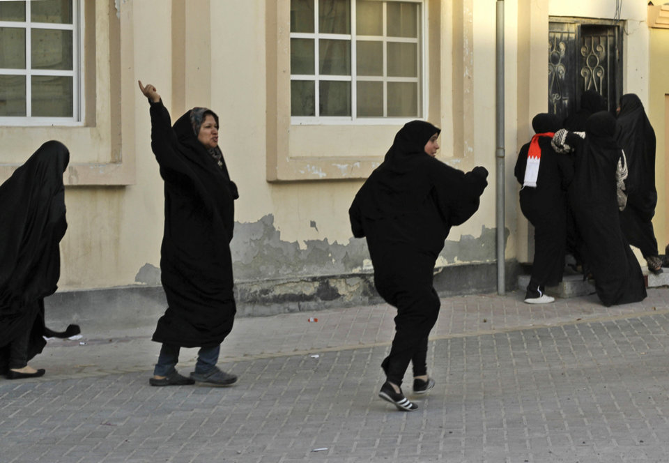 Photo -   Bahraini anti-government protesters run from riot police firing tear gas and stun grenades to disperse a demonstration in support of victims of torture in Buri, Bahrain, southwest of the capital of Manama, on Wednesday, June 27, 2012. Prominent Bahraini human rights activist Zainab al-Khawaja was shot in the leg with a tear gas canister and taken to a hospital by another activist. (AP Photo/Hasan Jamali)