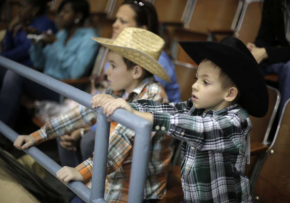 Caden Owens, 9, right, and his brother Teagen Owens, 6, both of Mustang, watch during the final performance of International Finals Rodeo at the State Fair Arena in Oklahoma City, Okla., Sunday, Jan. 20, 2013.  Photo by Garett Fisbeck, For The Oklahoman