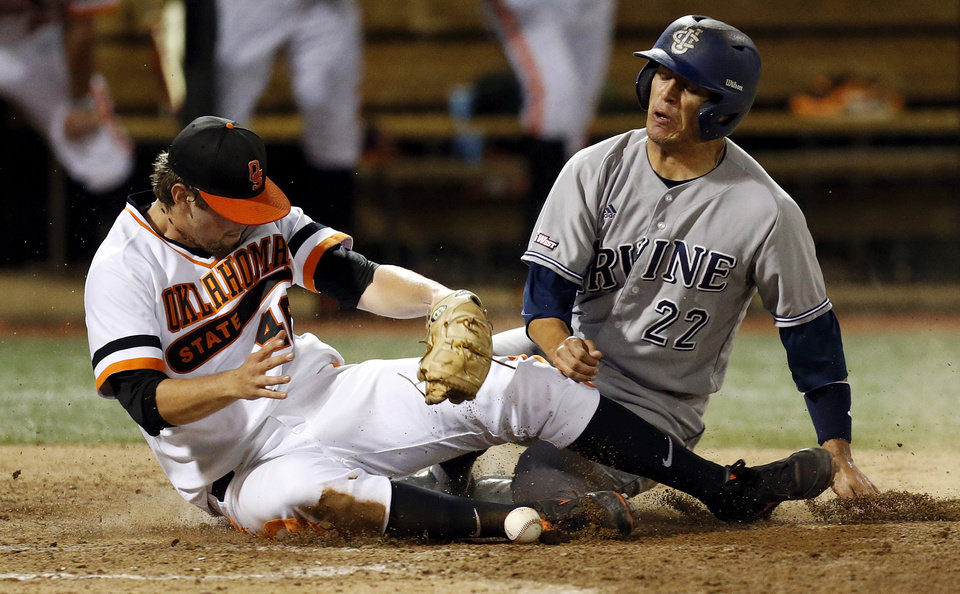 Photo - UC Irvine's Chris Rabago (22) slides home to score against OSU's Jon Perrin (46) in the 5th inning during Game 1 of the NCAA baseball Stillwater Super Regional between Oklahoma State and UC Irvine at Allie P. Reynolds Stadium in Stillwater, Okla., Friday, June 6, 2014. Photo by Nate Billings, The Oklahoman