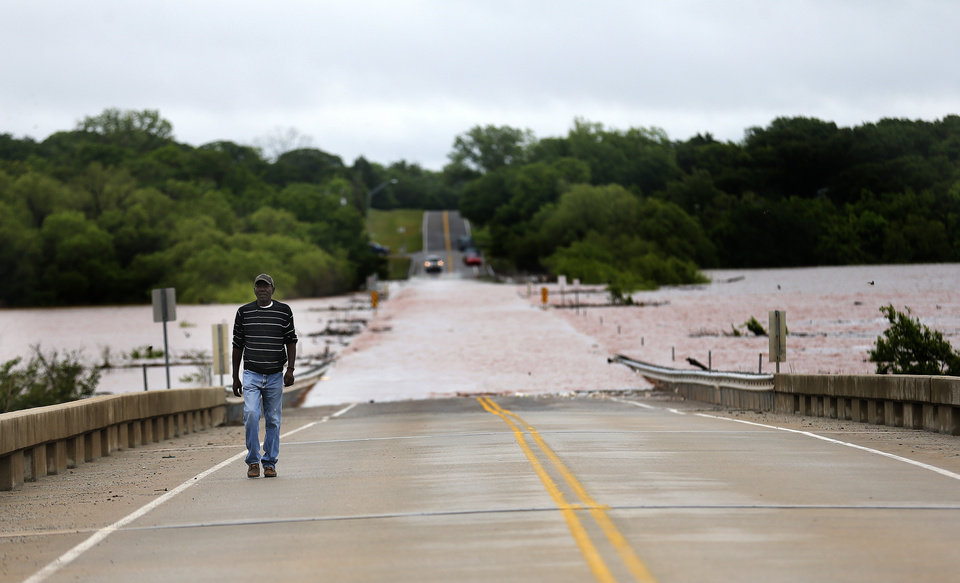 Photo - Darrell Knowles walks on the Alameda bridge over Lake Thunderbird in Norman, Okla., Sunday, May 24, 2015. Knowles frequently fishes the lake and has never see it this full. Photo by Sarah Phipps, The Oklahoman