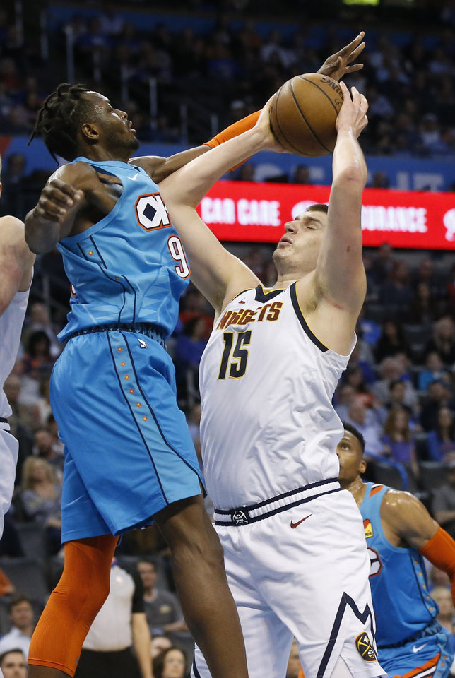 Photo - Denver Nuggets center Nikola Jokic (15) is fouled by Oklahoma City Thunder forward Jerami Grant (9) as he shoots during the first half of an NBA basketball game Friday, March 29, 2019, in Oklahoma City. (AP Photo/Sue Ogrocki)