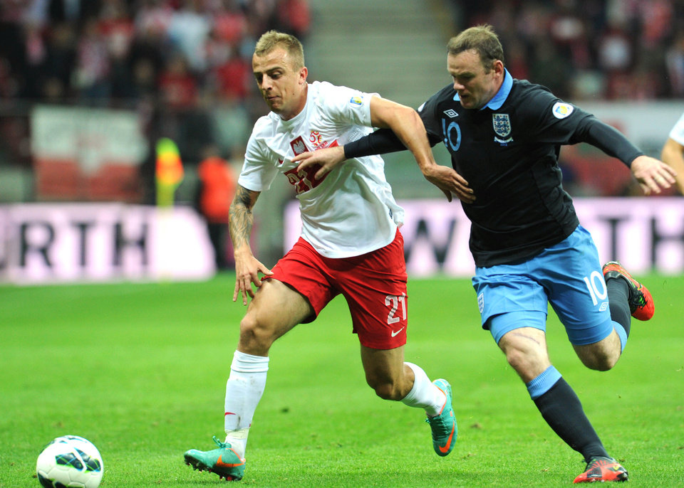 Photo -   Poland's Kamil Grosicki, left, is challenged by England's Wayne Rooney during their World Cup Group H qualifying soccer match at the National Stadium in Warsaw, Poland, Wednesday, Oct. 17, 2012. (AP Photo/Alik Keplicz)
