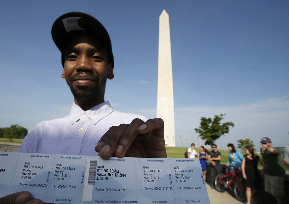 Photo - Visitor Roman Tanner displays his Washington Monument ticket, which are distributed at on a first-come basis at the Washington Monument in Washington, Monday, May 12, 2014, ahead of a ceremony to celebrate its re-opening. The monument, which sustained damage from an earthquake in August 2011, is reopening to the public today. (AP Photo)