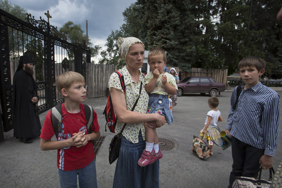 Photo - Olga Mikhailova, center, with her children arrive at the Russian Orthodox monastery in the Holy Dormition in Svyatogorskaya Lavra, 30 km, (19 miles) from Slovyansk, where they plan to stay during fighting between Ukrainian government forces and pro-Russian militants, Ukraine, Wednesday, May 28, 2014. The Mikhailova family have abandoned their home in Slovyansk to seek safety in the monastery.  In Slovyansk, a city 90 kilometers (55 miles) north of Donetsk which has seen repeated clashes over the past few weeks, with residential areas coming under mortar attack Wednesday from government forces. A school was badly damaged and other buildings were hit, according to residents, Wednesday, who told The Associated Press that several people were wounded.(AP Photo/Alexander Zemlianichenko)