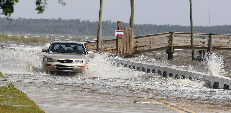 Photo - A motorist drives through a flooded street on Tuesday, Aug. 28, 2012, in Bay St. Louis, Miss.  Mandatory evacuation had been ordered by Tuesday in low-lying areas of all three Mississippi coastal counties, and waves were washing across beachside roads as Hurricane Isaac swirled offshore. All three coastal counties also set overnight curfews. The U.S. National Hurricane Center in Miami said Isaac became a Category 1 hurricane Tuesday with winds of 75 mph. It could get stronger by the time it's expected to reach the swampy coast of southeast Louisiana. (AP PhotoJohn Bazemore) ORG XMIT: MSJB102