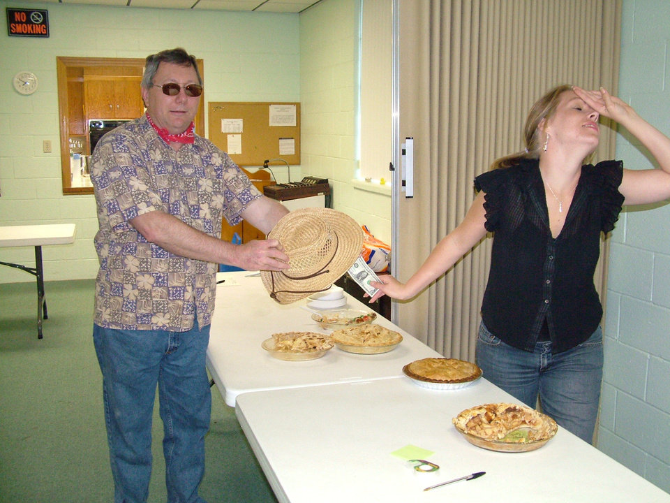 Apple pie baker Dave Archer attempts to swing Judge Kim Goshorn's vote for Prettiest Pie at the Harrah United Methodist Church's first annual F3 (Fry Fish Fry). Unfortunately the miscreant attempted to bribe the judge with a mere dollar bill and the judge decided that she could not be bought but confiscated the buck anyway to donate to the church's signage fund.<br/><b>Community Photo By:</b> Lin Archer<br/><b>Submitted By:</b> Lin,