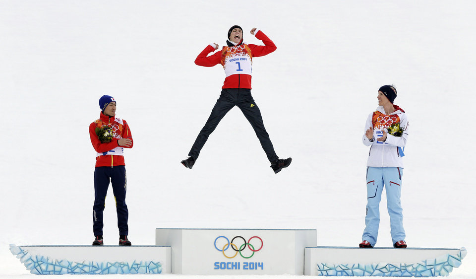 Photo - Germany's Eric Frenzel celebrates winning the gold as he is flanked by Japan's silver medal winner Akito Watabe, left, and Norway's bronze medal winner Magnus Krog during the flower ceremony after the cross-country portion of the nordic combined at the 2014 Winter Olympics, Wednesday, Feb. 12, 2014, in Krasnaya Polyana, Russia. (AP Photo/Matthias Schrader, File)