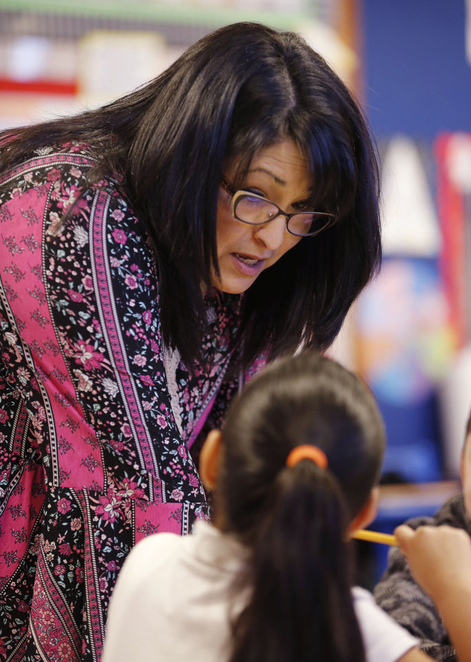 Photo -  First-grade teacher Tiffany Olvera works with her students Tuesday. [Photo by Paul Hellstern, The Oklahoman]