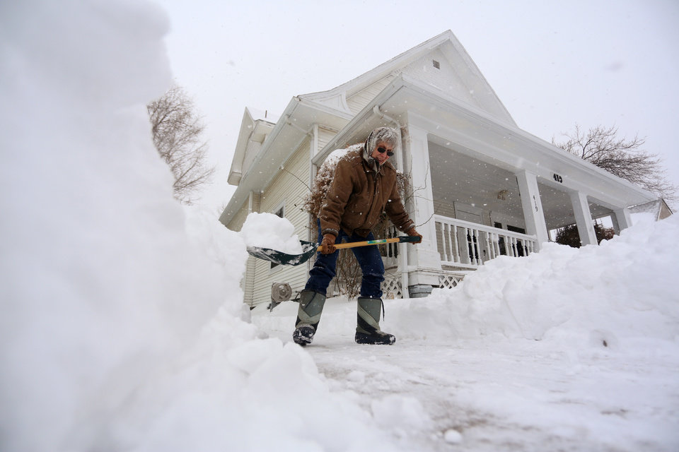 Virginia Hawkins shovels snow from her driveway Thursday, Feb. 21, 2013, in Hutchinson, Kan. A winter storm dumped more than a foot of snow in the city of Hutchinson from Wednesday morning through Thursday.  (AP Photo/The Hutchinson News, Travis Morisse)