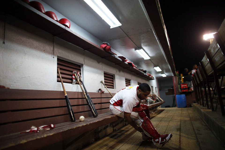 In this Dec. 29, 2012 photo, Roberto Pena straps on his leg guards prior to a game in Caguas, Puerto Rico. The island has seen a resurgence of interest in baseball after 17-year-old shortstop Carlos Correa became the first Puerto Rican to be the first overall pick in this year's draft, receiving a $4.8 million signing bonus with the Houston Astros in June.  (AP Photo/Ricardo Arduengo)