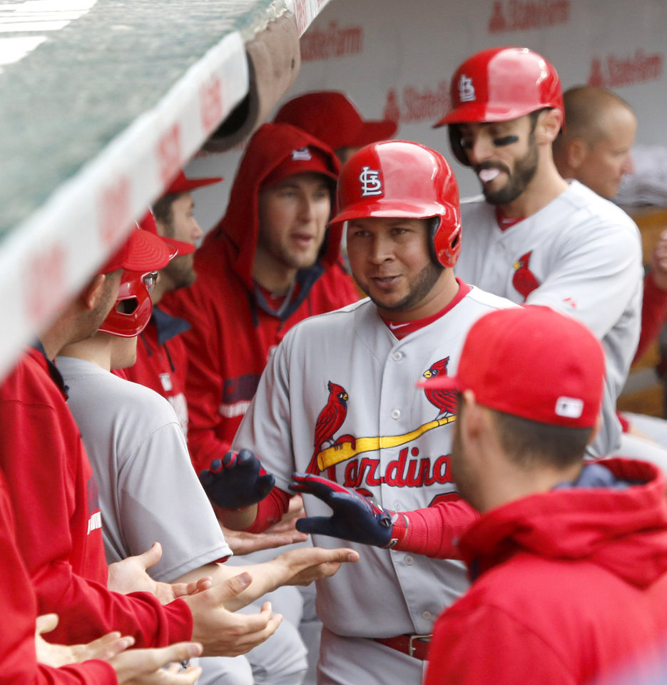 Photo - St. Louis Cardinals' Jhonny Peralta, center, is congratulated in the dugout after hitting a two-run home run off Chicago Cubs relief pitcher Justin Grimm during the eighth inning of a baseball game Friday, May 2, 2014, in Chicago. Teammate Matt Carpenter, background right, also scored on the hit. (AP Photo/Charles Rex Arbogast)