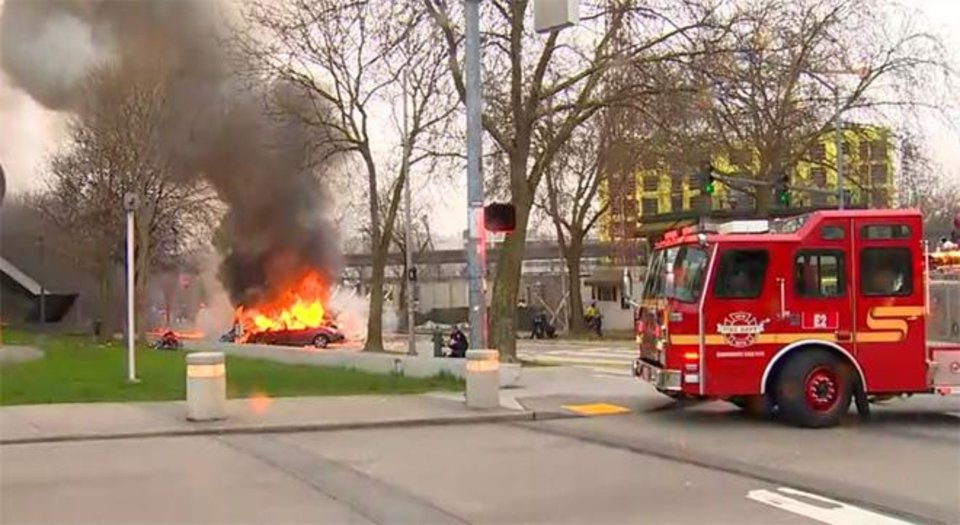 Photo - In this image made from video provided by KOMO-TV, smoke rises from the scene of a news helicopter crash outside the KOMO-TV studios near the space needle in Seattle, Tuesday, March 18, 2014, in Seattle. The station says the copter was apparently coming in for a landing on its rooftop Tuesday morning when it possibly hit the side of the building and went down, hitting several vehicles. (AP Photo/Courtesy KOMO-TV) MANDATORY CREDIT