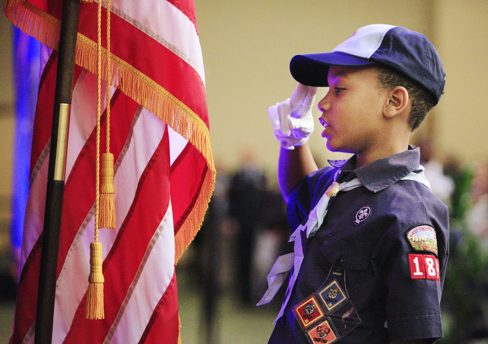 Photo - Markel Kendrick, 9, of Midwest City, salutes the flag during the presentation of the colors by Cub Scout Pack 1864 at the 17th annual Midwest City Dr. Martin Luther King Jr. Prayer Breakfast on Monday in Midwest City.   PAUL B. SOUTHERLAND - PAUL B. SOUTHERLAND