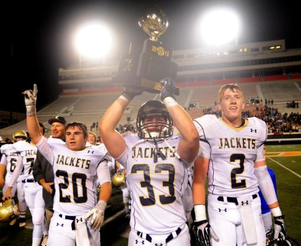 Photo -  Kingfisher players Tristan Ransom (center), Tanner Rutledge (left) and Jace Sternberger (right) celebrate winning the Class 3A state championship in 2013. [Oklahoman archives]
