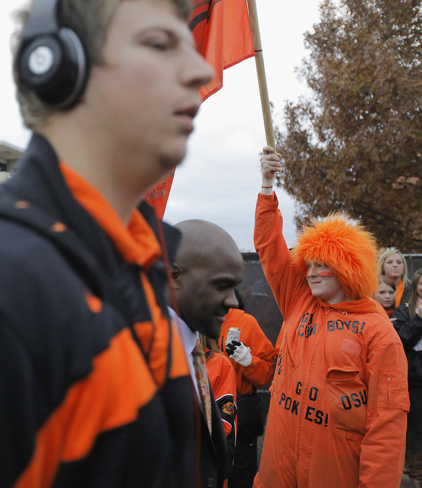 Photo - An Oklahoma State fan cheers on the Cowboys in the 'Spirit Walk' before the Bedlam college football game between the Oklahoma State University Cowboys (OSU) and the University of Oklahoma Sooners (OU) at Boone Pickens Stadium in Stillwater, Okla., Saturday, Dec. 3, 2011. Photo by Chris Landsberger, The Oklahoman