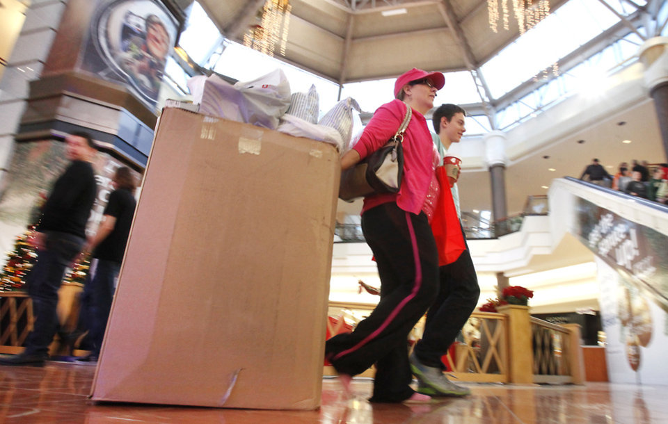 Black Friday shoppers at Penn Square Mall lug purchases in a big cardboard box. Photo by David McDaniel, The Oklahoman Archives