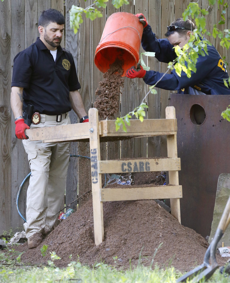 Photo - Oklahoma State Bureau of Investigation officials search through dirt and debris at a home in Oklahoma City, Monday, April 10, 2017, where they are using ground-penetrating radar to look for remains in connection with the Carina Saunders murder. The body of the 19-year-old woman was found dismembered a duffle bag in October of 2011. (AP Photo/Sue Ogrocki)