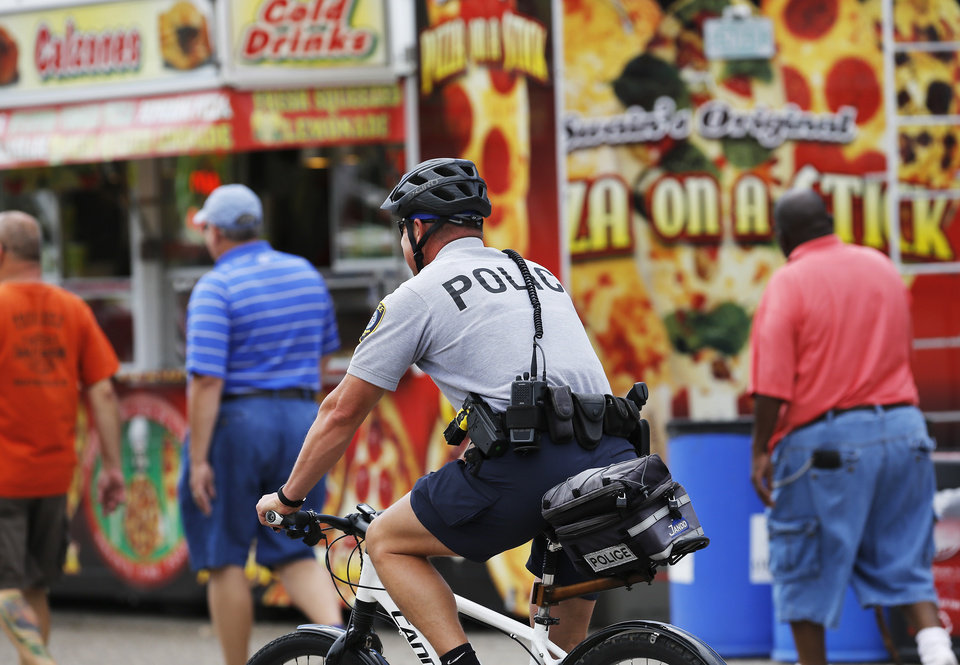 Photo - An Oklahoma City police officer patrols the midway at the Oklahoma State Fair on a bicycle on Wednesday, Sep. 18, 2013. Photo  by Jim Beckel, The Oklahoman.