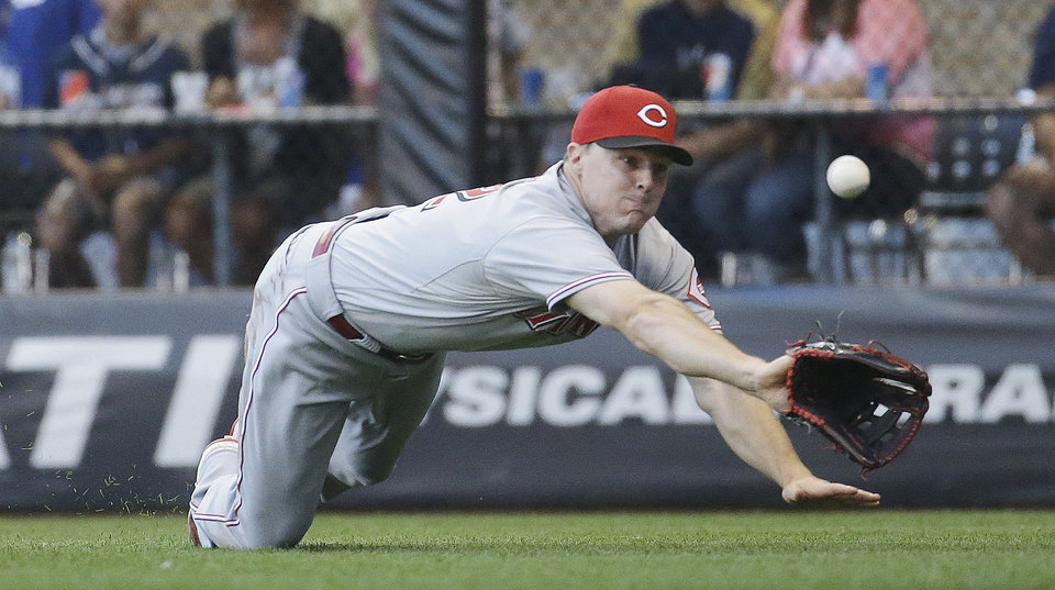 Photo - Cincinnati Reds' Jay Bruce dives but can't catch a ball hit by Milwaukee Brewers' Carlos Gomez during the fifth inning of a baseball game Wednesday, July 23, 2014, in Milwaukee. (AP Photo/Morry Gash)