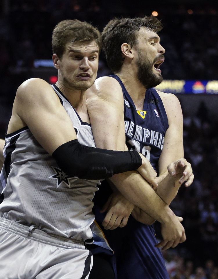 Photo - San Antonio Spurs' Tiago Splitter, left, of Brazil, and Memphis Grizzlies' Marc Gasol, right, of Spain, get tangled up as they chase a loose ball during the second half in Game 1 of a Western Conference Finals NBA basketball playoff series Sunday, May 19, 2013, in San Antonio. (AP Photo/Eric Gay)
