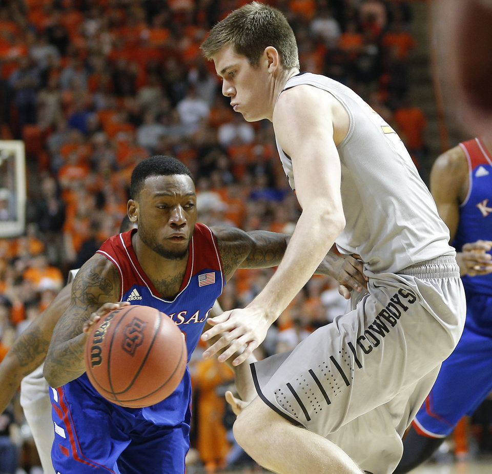 Photo - Kansas' Naadir Tharpe (10) goes past Oklahoma State's Mason Cox (53) during an NCAA college basketball game between Oklahoma State University (OSU) and the University of Kansas at Gallagher-Iba Arena in Stillwater, Okla., Saturday, March 1, 2014. Photo by Bryan Terry, The Oklahoman