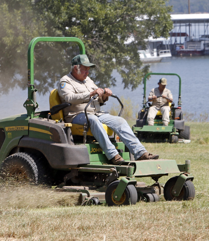 Photo - State employees Oddie Dean and Tony Palmer mow Wednesday at Lake Thunderbird in Norman. More than 400,000 Oklahomans are expected to travel over the weekend.  Photo by Steve Sisney, The Oklahoman  Steve Sisney - STEVE SISNEY