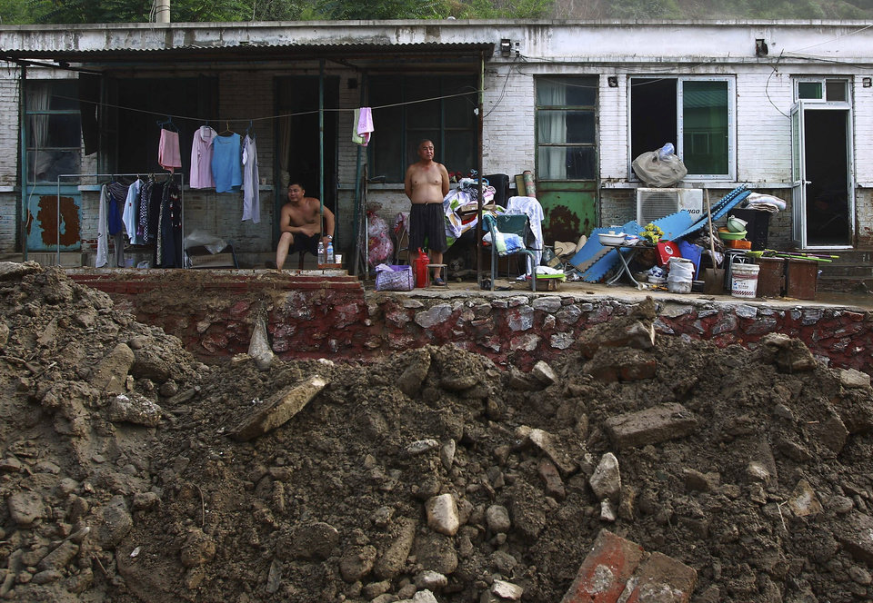 Photo -   In this photo taken on Monday, July 23, 2012, Chinese villager look at courtyard damaged by flood at their home in Fangshan district in Beijing. Recent heavy rains across much of China have left nearly 100 people dead, state media said Tuesday. More than a third of the fatalities were in the flood-ravaged capital, where some residents questioned whether the city's rapid push for modernization came at the expense of basic infrastructure such as drainage networks. (AP Photo) CHINA OUT