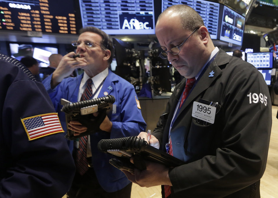 Photo - Traders Sal Suarino, left, and Jeffrey Vazquez work on the floor of the New York Stock Exchange, Wednesday, Feb. 26, 2014. The stock market is little changed as investors pick over more earnings reports from retailers and other U.S. companies. (AP Photo/Richard Drew)