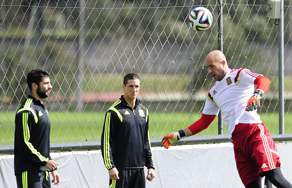 Photo - Spain's Raul Albiol, left, Fernando Torres, center, and goal keeper Pepe Reina during an official training session the day before the group B World Cup soccer match between Spain and Australia at the Atletico Paranaense training center in Curitiba, Brazil, Sunday, June 22, 2014. Spain will play in group B of the Brazil 2014 World Cup. (AP Photo/Manu Fernandez)