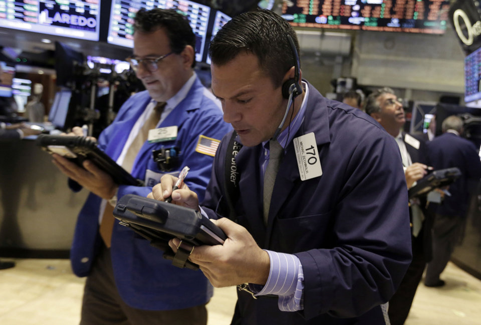 Photo - Trader Michael Zicchinolfi, center, works on the floor of the New York Stock Exchange Monday, July 22, 2013. The stock market is opening mixed after McDonald's reported poor quarterly earnings. (AP Photo/Richard Drew)