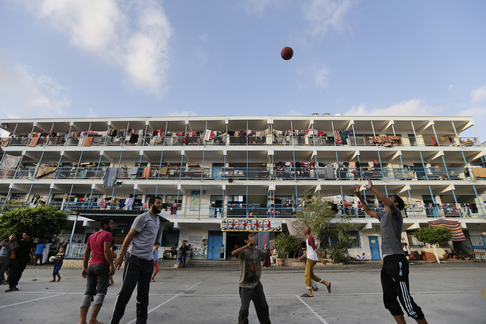 Photo - Palestinian displaced people play in the courtyard of a U.N. school at Jebaliya refugee camp, in the northern Gaza Strip, Tuesday, July 29, 2014. The school is one of dozens of emergency shelters for those who have fled the fighting. About 180,000 Palestinians_about 10 percent of the entire population of Gaza_are seeking shelter in over 80 UNRWA schools, according to United Nations' Office for the Coordination of Humanitarian Affairs' July 28 report. (AP Photo/Lefteris Pitarakis)