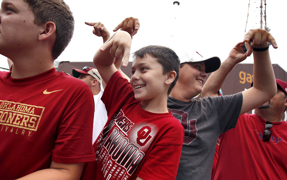 Photo - Kade Webber , center, gives the horns down sign as the Texas football team arrives during the Red River Rivalry college football game between the University of Oklahoma Sooners (OU) and the University of Texas Longhorns (UT) at the Cotton Bowl Stadium in Dallas, Saturday, Oct. 12, 2013. Photo by Chris Landsberger, The Oklahoman