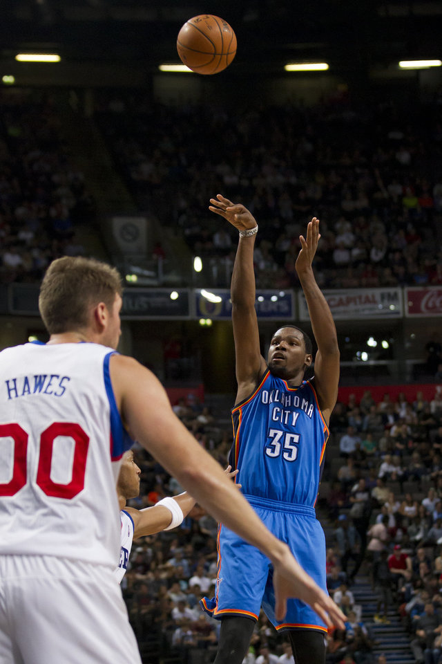 Photo - Oklahoma City Thunder's Kevin Durant, right, takes as shot as Philadelphia 76ers' Spencer Hawes looks on during their NBA preseason basketball game at the Phones4 u Arena in Manchester, England, Tuesday, Oct. 8, 2013. (AP Photo/Jon Super) ORG XMIT: MJS111