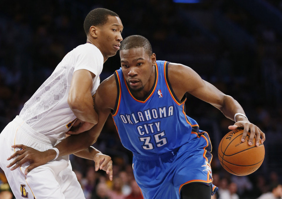 Photo - Oklahoma City Thunder small forward Kevin Durant, right, drives with the ball as Los Angeles Lakers small forward Wesley Johnson defends agaisnt him during the first half of an NBA basketball game in Los Angeles, Sunday, March 9, 2014. (AP Photo/Danny Moloshok)