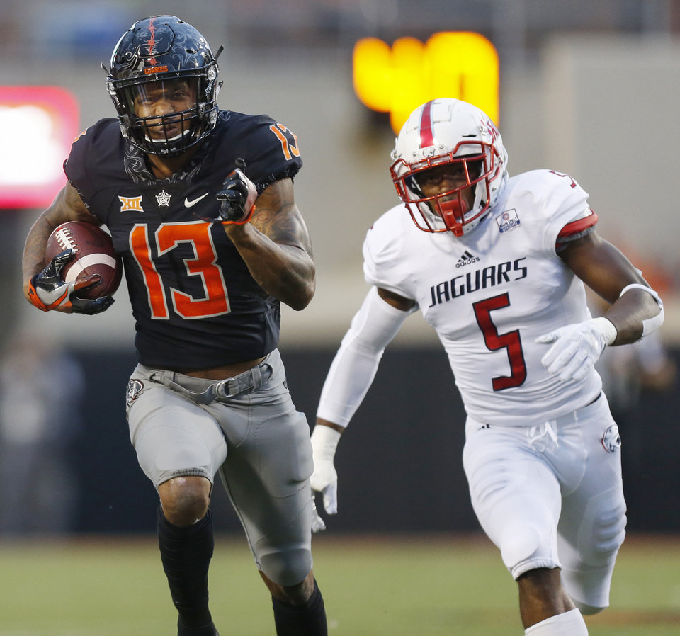 Photo - Oklahoma State's Tyron Johnson (13) runs after a catch in the first quarter in front of South Alabama's Malcolm Buggs (5) during a college football game between Oklahoma State (OSU) and South Alabama at Boone Pickens Stadium in Stillwater, Okla., Saturday, Sept. 8, 2018. Photo by Nate Billings, The Oklahoman