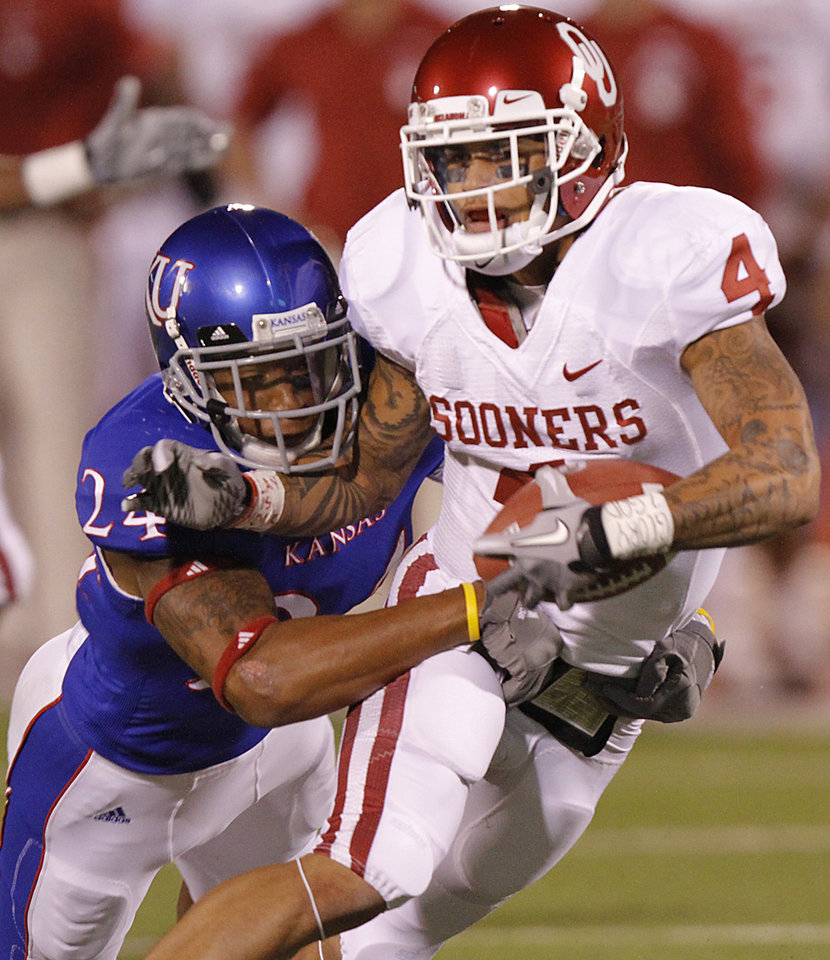 Oklahoma\'s Kenny Stills (4) makes a catch in front of Kansas\' Bradley McDougald (24) during the college football game between the University of Oklahoma Sooners (OU) and the University of Kansas Jayhawks (KU) on Saturday, Oct. 15, 2011. in Lawrence, Kan. Photo by Chris Landsberger, The Oklahoman