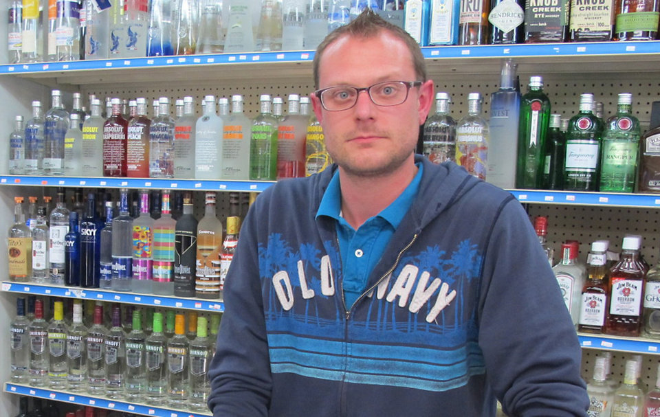 Photo - In an Oct. 14, 2013 photo, George Nemetz, manager of Mahoney's Spirits & Edibles in Traverse City, Mich., stands behind the counter of his downtown shop. Nemetz says town festivals are good for business and disagrees with local residents who think they've gotten out of hand. (AP Photo/John Flesher)